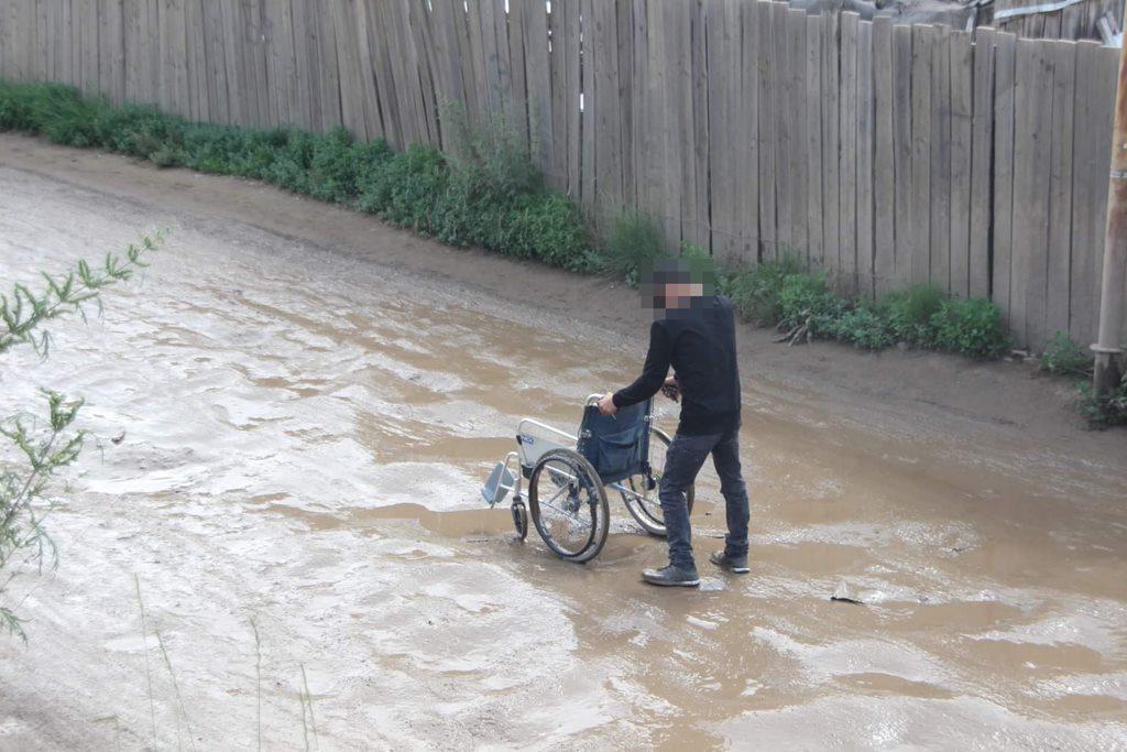 A person pushing a wheelchair down a muddy track